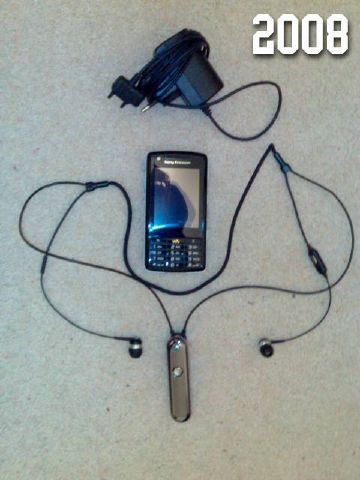 Photo of a Sony Ericsson W960i smartphone, a Bluetooth headset and a single charger