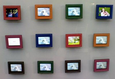 12 digital picture frames hanging on a wall, each with a different colour frame