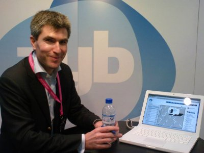 A man standing next to a laptop showing the Zyb website
